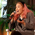 Asian woman with pink hair in black hair bow and grey plaid blazer and grey and black patterned skirt holding black microphone and sitting on white chair in front of green plants and white screen and orange wall