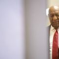 Bill Cosby, wearing a red tie and blue jacket, grimaces in the corridor of a Pennsylvania courthouse.