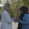 Brown woman in brown hijab and grey shirt next to Brown woman in black hijab and blue shirt in front of green trees and grey pavement