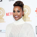 Black woman with black and brown hair in white sweater in front of white wall with red and black and gold logos