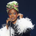 Black woman in green and pink head wrap and black blouse with white feather sleeves hold black microphone in front of wall with blue light