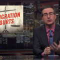 """John Oliver. White man sits at desk in dark suit with blue tie and red and blue checked shirt. Graphic beside him reads, """"Immigration Courts."""""""