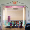 Puerto Rican children sit in a shelter sitting on a light blue bench two of the children are playing with a phone the other three are watching.