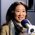 Asian woman with in brown blazer and scarf with blue text and black headphones behind blue and white microphone and black stand in front of navy and grey walls