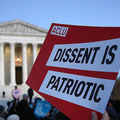 """A hand holds a red and white sign that reads, """"Dissent is patriotic."""" The Supreme Court is in the background."""