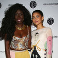 Bozoma Saint John and Zendaya. Dark-skinned Black woman with long black hair, bright smile, gold necklace and sequined bustier stands beside light-skinned Black woman with hair in ponytail wearing hoop earrings and white dress with illustrated character
