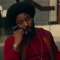 Black man with black afro and beard in red sweater holding black phone  in front of grey stairwell and wall and brown doors