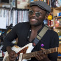 Black man in black shirt and sunglasses and grey derby cap holds white and brown guitar in front of brown and black shelves with multicolored books and records and other items