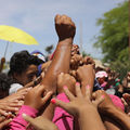 Brown hands join together in a huddle outside. A fist bursts through the huddle and is raised into the air.
