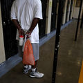 A Black man wearing a white shirt and gray shorts stands with his hands in cuffs, holding an orange mesh bag and a white and red bottle