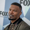 Jamie Foxx. Black man with black hair and goatee in cheetah-print shirt and green jacket smiles in front of wall with green and blue and white triangles and black text