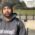 Black man with black beard in grey hat and hoodie with white text and black backpack in front of white building and green lawn and trees and black fence