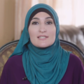 Linda Sarsour. White-skinned woman wears green hijab and purple shirt, looks directly at camera