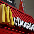 Yellow and white McDonald's sign on red restaurant roof