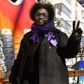 Black man with black afro and beard wears shirt and jacket with purple Prince symbol and heart and scarf and sunglasses in front of Black man in black jacket with purple scarf and hat and brown cymbal and orange guitar prop and brown buildings