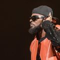 Black man with black beard in black and gold sunglasses and black hat and black and red leather jacket in front of black screen
