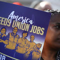 Black woman at a rally holds a purple sign with yellow text that says America needs union jobs with an illustration of public sector workers