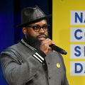 Black man with black beard in black fedora and brown sunglasses and grey jacket with black and white cuffs holds black microphone in front of blue curtain and yellow screen with blue text
