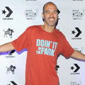 Brown man with grey beard in red t-shirt in front of white wall with black text and insignia