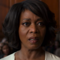 Black woman with black hair in beige dress in front of courtroom audience and brown wall