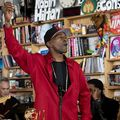 Black man in red sweatshirt and black hat and shirt in front of White and Black men in black clothing and brown bookshelf and grey wall