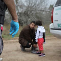 A border patrol agent at the foreground, only shown are a gun hoisted at his pants and his right hand wearing a blue rubber glove. An immigrant man kneels down at an immigrant child. A border patrol car is to their right.