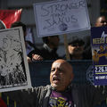 """A Brown man holds up a sign that says """"Right to work. We all lose."""""""