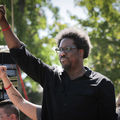 Black man with black afro in black shirt and glasses raises fist in front of green trees