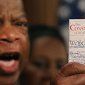 """John Lewis. Black man holds small booklet with """"The Constitution of the United States"""" on the front."""