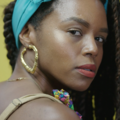 Black woman with black dreadlocks in front of yellow background