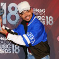 Chance the Rapper smiles in grey hat and blue jacket with white detail while holding silver award in front of red background with white text