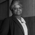 Black-and-white image of Ida B. Wells in black jacket and white shirt in front of wood wall