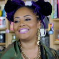 Lalah Hathaway with black and purple dreadlocks in gold jewelry and green and brown camouflage and grey shirt in front of Black woman with black hair and t-shirt and brown bookshelf