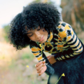 Yara Shahidi with black hair in black and yellow tie-dye shirt and black skirt holding yellow flower with green stem in front of green and brown background