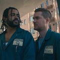 Daveed Diggs with black dreadlocks and beard in navy moving company uniform next to Rafael Casal with brown hair in navy moving company uniform in front of brown building