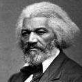 Black-and-white image of Black man with black and grey hair in black and white formal attire in front of grey wall