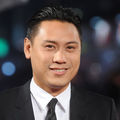 Jon M. Chu with black hair in black suit in front of dark background
