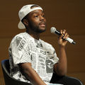 Kid Fury in blue jeans and white and black shirt and hat hold black microphone while sitting in black chair in front of brown wood wall
