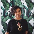 Loveis Wise with black dreadlocks in black shirt and gold necklace in front of grey wall with green leaves painted on top