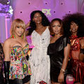 "Cast of ""Pose"" and Janet Mock in multicolored outfits in front of room bathed in purple light"