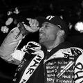 Black-and-white photo of Prodigy in leather jacket with black and white text and black hat with white text while holding black microphone
