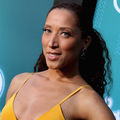 Robin Thede with brown hair and green eyes in red dress in front of blue wall with white text