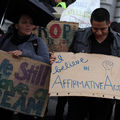 "Brown people protest outside. One board cardboard sign reads, ""I believe in affirmative action."""