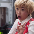 Awkwafina. Asian-American woman with blond hair, wearing red and white top