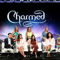 """Cast and creators of """"Charmed"""" sit on two-tiered black stage in multicolored clothing in front of purple background"""