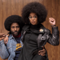Lauren Harrier with black afro raises fist in black leather jacket and sweater while seated on John David Washington with black afro in blue denim jacket and navy sweater in front of brown wall