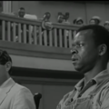 Black-and-white image of Brock Peters in shirt and overalls next to Gregory Peck in glasses and suit in front of courthouse with Black audience members in top balcony