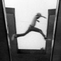 Black-and-white image of man jumping gap between building wings