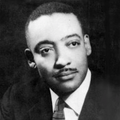 Black-and-white photograph of Louis E. Lomax in suit and tie in front of black background