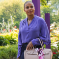 Sanaa Lathan with shaved head in purple blouse and navy skirt holding brown bag in front of green flowers
